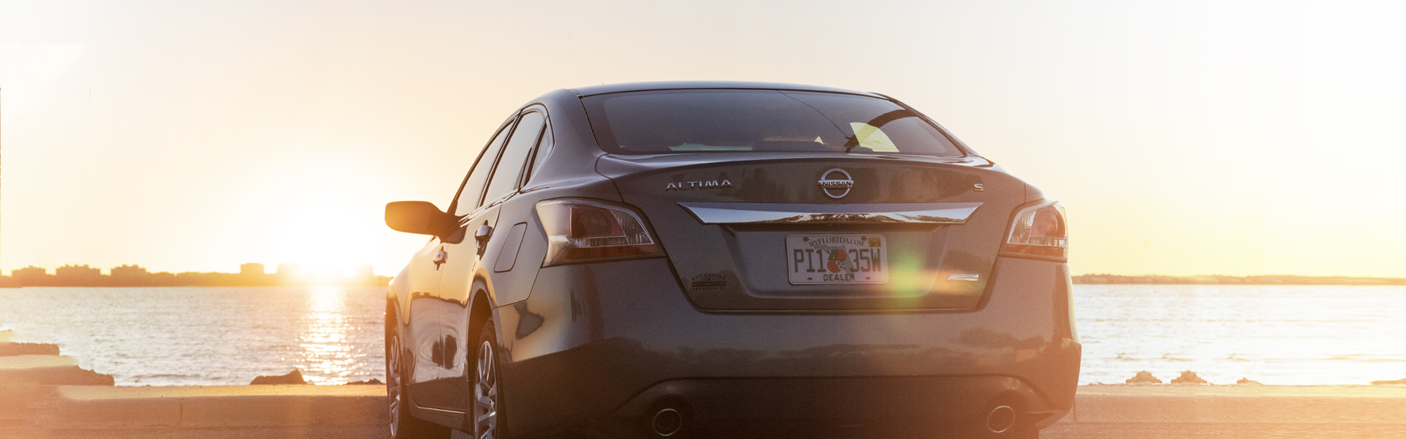 Used Nissan Altima car for sale parked at Sarasota Bay at sunset